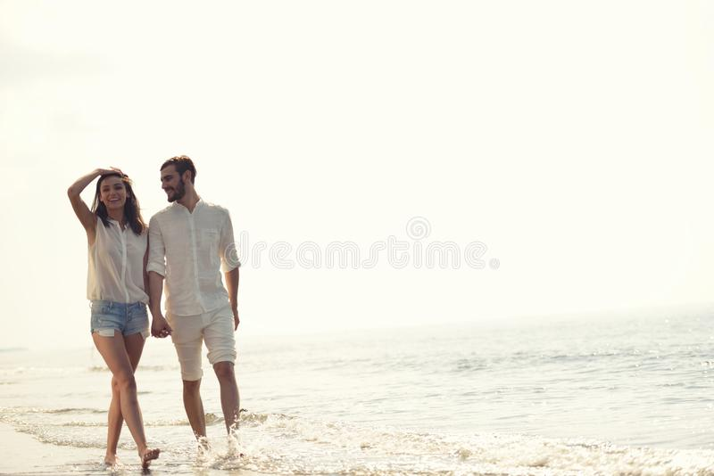 Happy fun beach vacations couple walking together laughing having fun on travel destination. Beach summer vacation couple running on holidays. Happy fun beach royalty free stock image