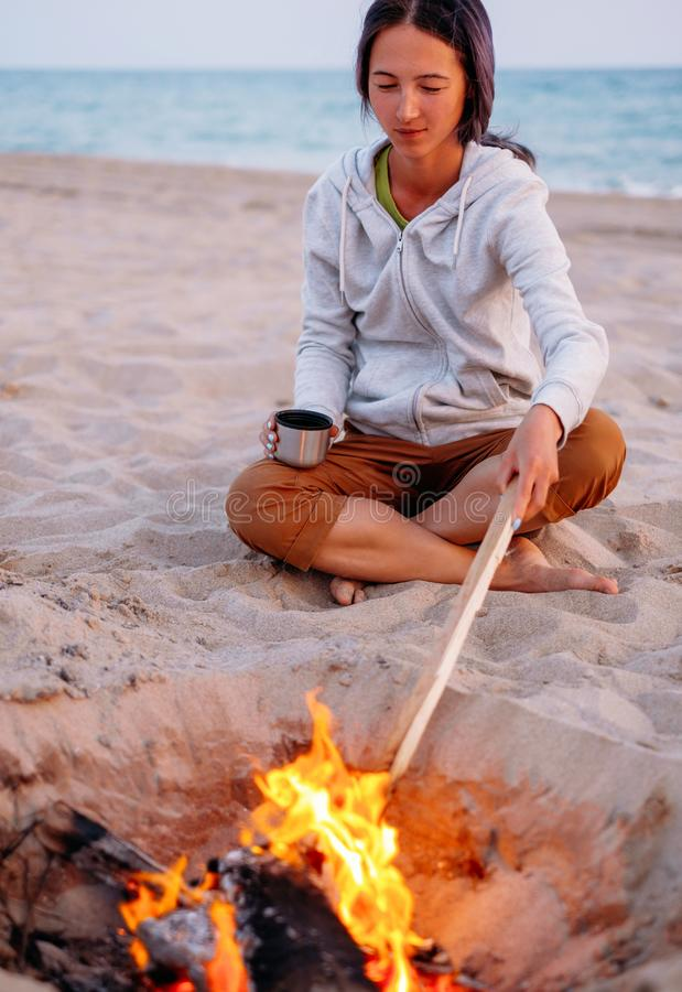 Woman relaxing near a campfire on beach. royalty free stock photography