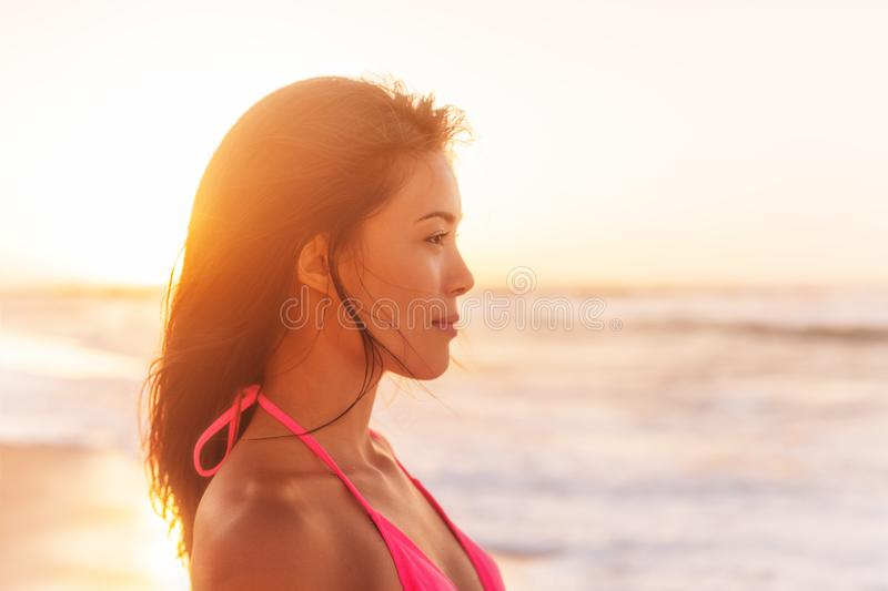 Beach sunset beautiful young Asian woman relaxing pensive profile at sun glow looking over ocean on beach. Chinese girl in pink. Bikini happy royalty free stock images