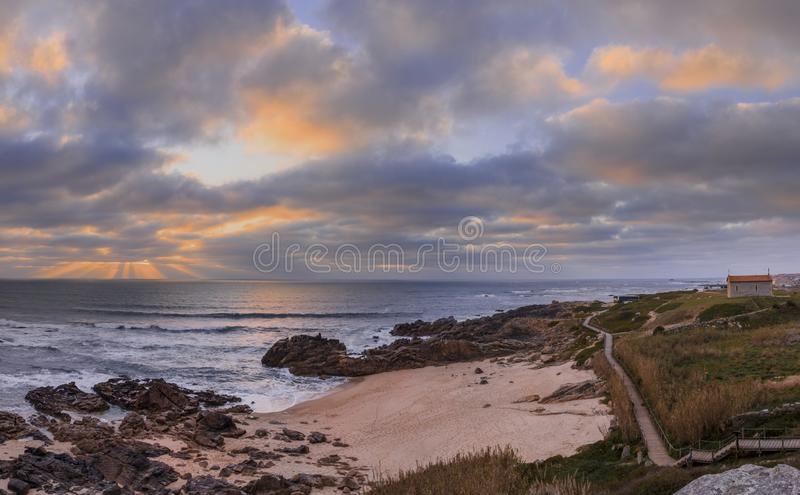 Beach with sunset rays between the thick clouds stock photo