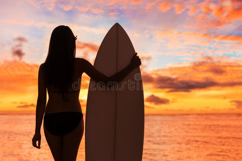 Beach sunset sexy surfer woman surfing lifestyle relaxing holding surfboard looking at ocean waves for surf. Active. Healthy living silhouette of sports athlete stock image