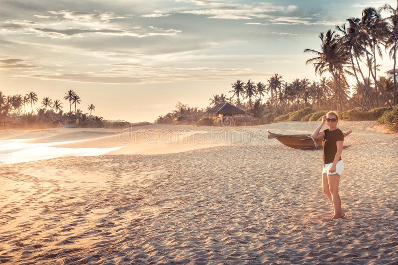 Beach sunset travel vacation lifestyle landscape with woman on wide sand coastline with palm trees with scenic orange sunset sky royalty free stock photo