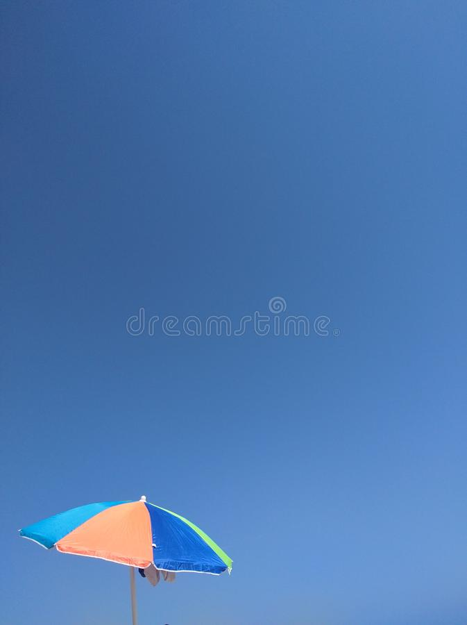 Beach tanning umbrella on a blue sky stock photo