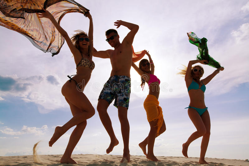 Beach teens party. Large group of young people enjoying a beach party stock images