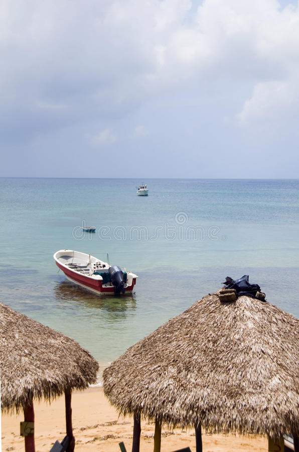 Beach thatch roof restaurant huts with fishing boat Caribbean Se stock photography