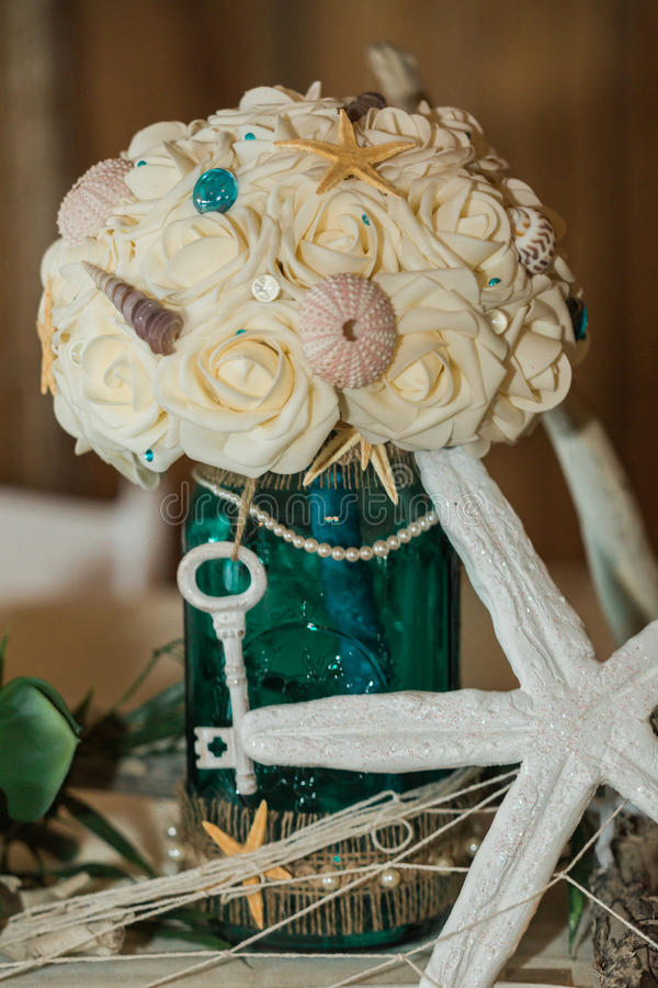 Beach Themed Ocean Wedding Reception Centerpiece with Floral Bouquet and Key. Cute, Fun, Handmade. Beach Themed Ocean Wedding Reception Decorations. Party royalty free stock image