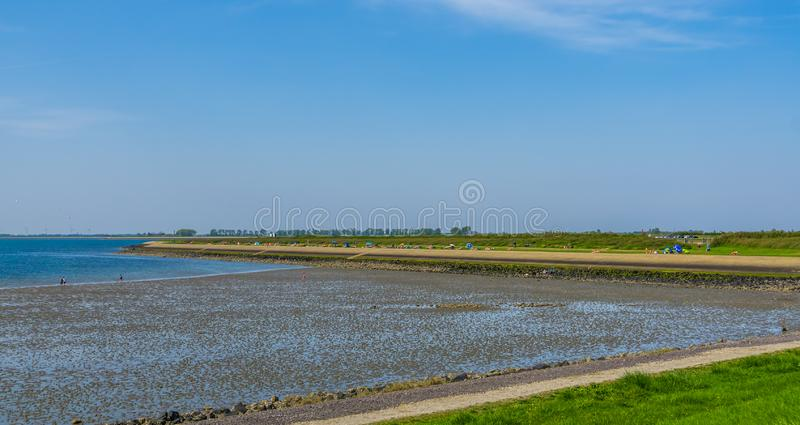 The beach of tholen with visitors, popular beach in zeeland, Bergse diepsluis, Oesterdam, The Netherlands. Beach of tholen with visitors, popular beach in royalty free stock photos