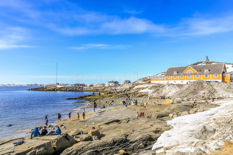 Beach time for Inuit people enjoying the sunny May day at the sea fjord, Nuuk city, Greenland. Active arctic buildings climate cold crowd daylight destinations royalty free stock photo