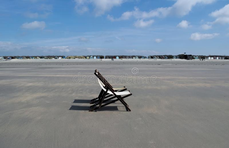 A beach to yourself. Long stretch of sand at low tide and two deck chairs on a quiet beach. A row of beach huts line where the beach begins royalty free stock photography