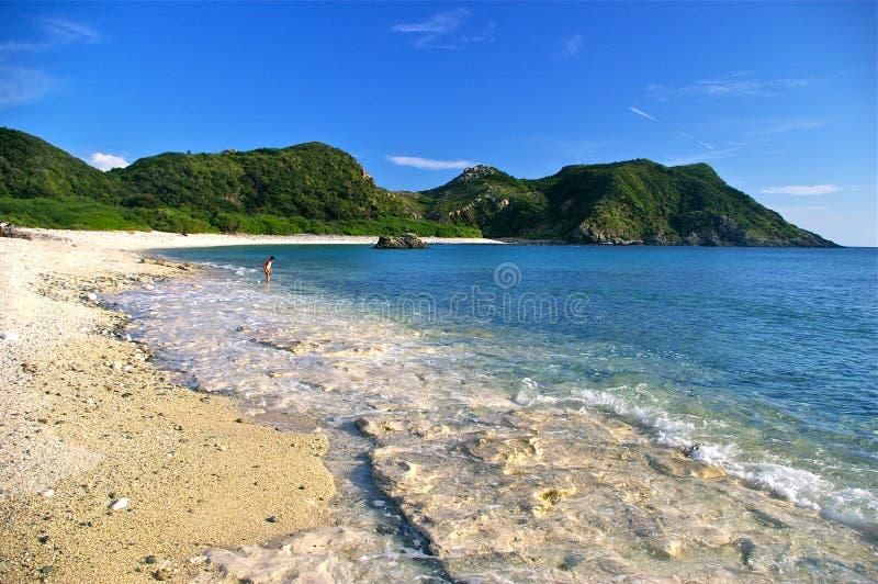 Beach on Tokashiki Island. A boy wades in the warm water of a beach on Tokashiki Island in Okinawa, Japan stock photo