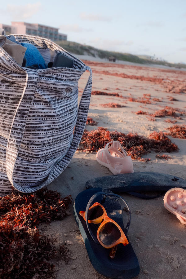 Beach Tote. Shoes and sunglasses on the shore royalty free stock images