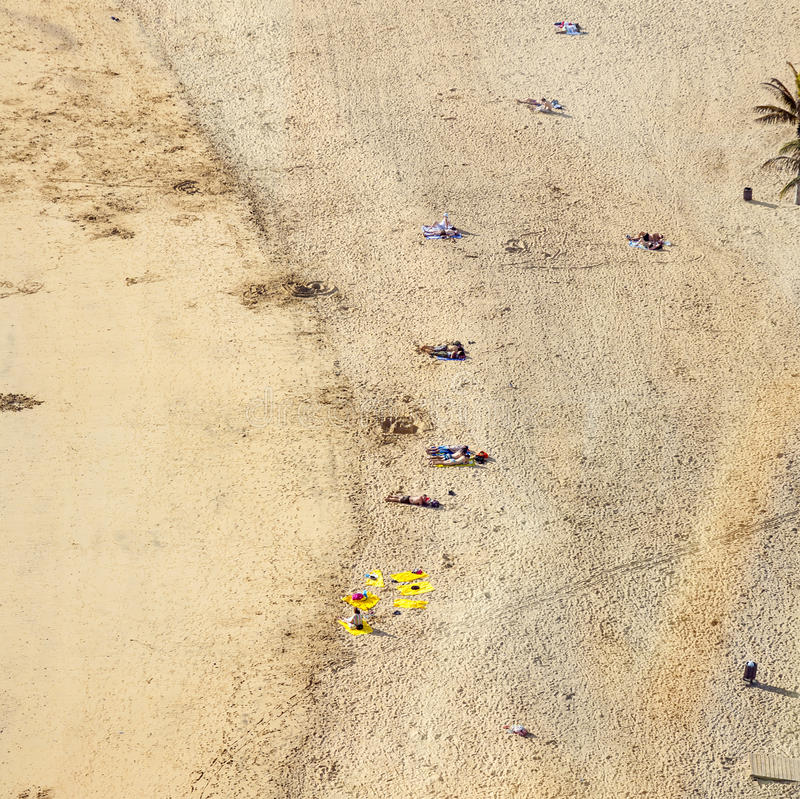 Beach with tourists in summer in Arrecife, Spain. Beach El Reducto is granted a blue flag by the European Union. This seal for cleanness must renewed yearly stock image