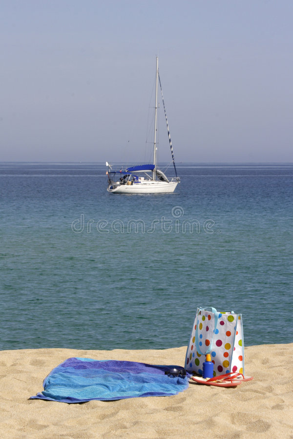 Beach towel and bag with yacht stock photography