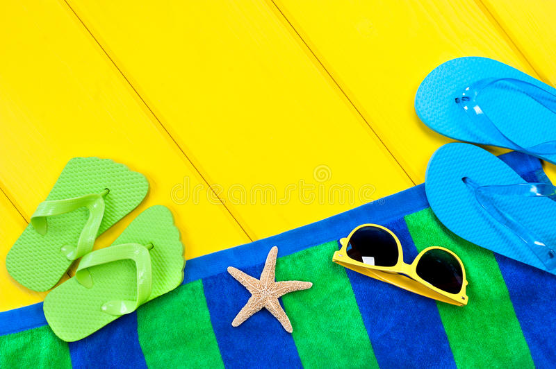 Beach towel on deck. A beach towel, flip flops and sunglasses on a colorful yellow wooden deck with the presence of a starfish to insinuate a beach relates stock photos