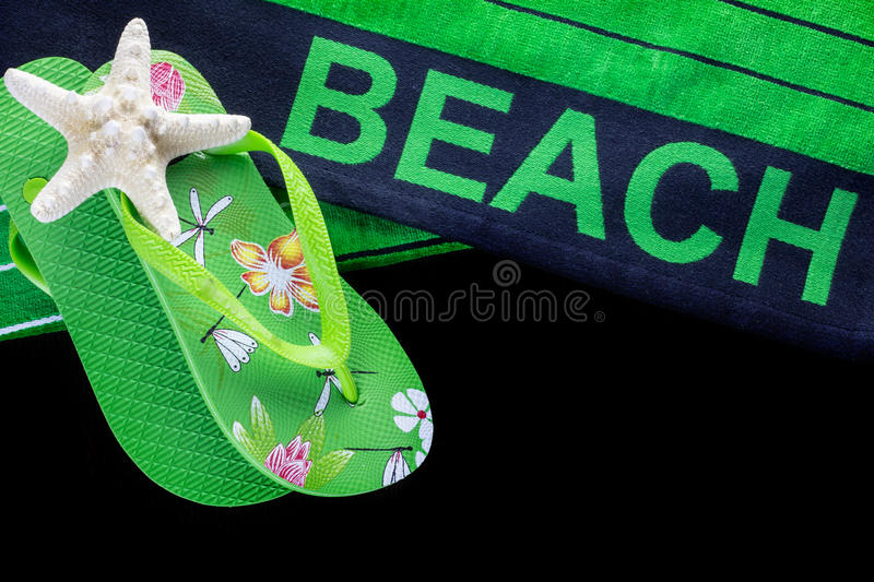 Beach towel with flip flops stock photography