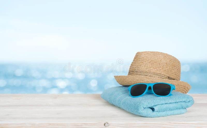 Beach towel, sunglasses and hat on wood over blurred seascape royalty free stock images