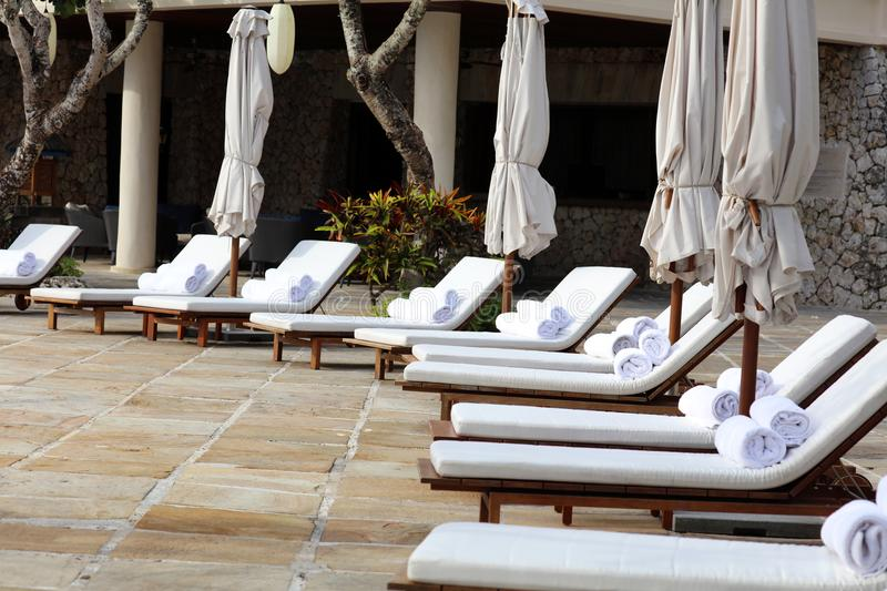 Beach towels at tropical resort and seats for laying in the sun at luxury hotel stock images