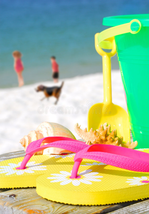 Beach toys and family playing stock images