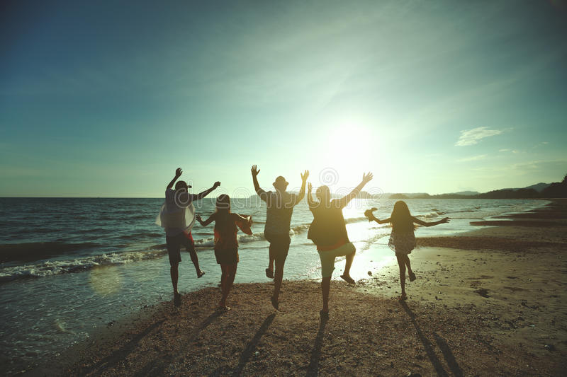 Beach travel. Asian family running on background of sunset beach and sea stock photo
