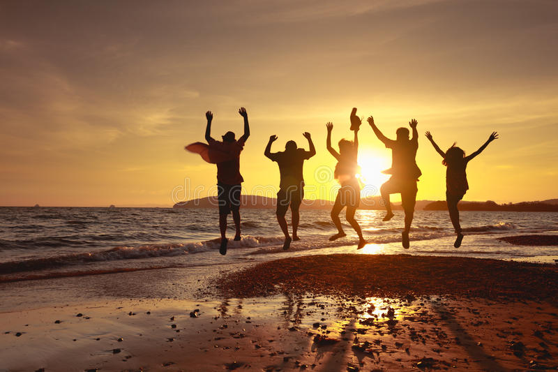Beach travel. Asian family running on background of sunset beach and sea royalty free stock image