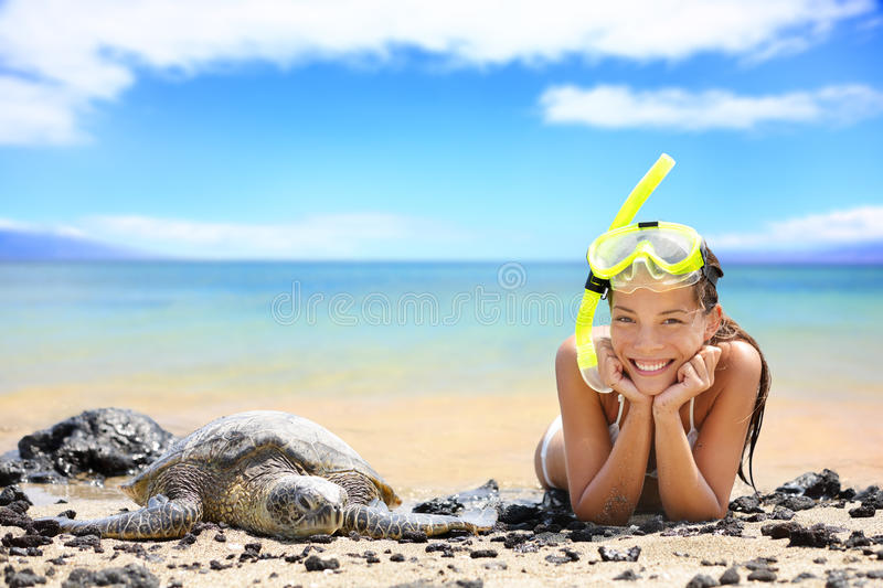 Beach travel woman on Hawaii with sea sea turtle. Snorkeling girl on vacation wearing snorkel smiling happy enjoying blue sky and sun lying next to Hawaiian stock photo
