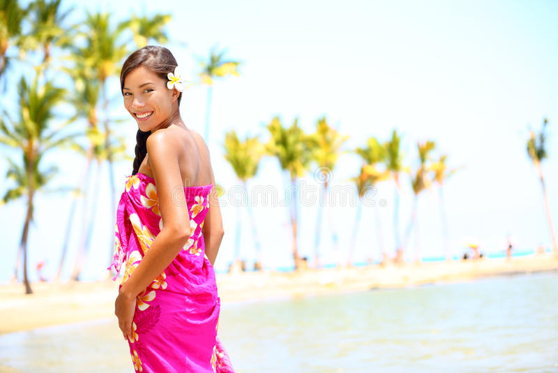 Beach travel - woman smiling happy on Hawaii. Girl in sarong cheerful on sunny hawaiian palm tree beach on holiday resort vacation. Big Island, Hawaii, USA royalty free stock photo