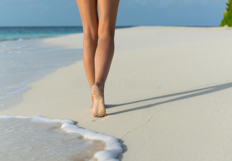Beach travel - woman walking on sand beach leaving footprints in the sand. Closeup detail of female feet royalty free stock photography