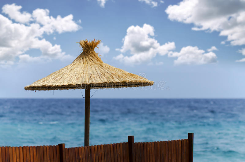Beach umbrella. Straw beach umbrella with beautiful cloudscape background royalty free stock images