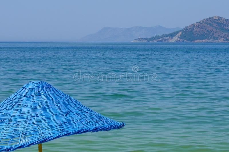 Blue umbrella against the line of the sea horizon. Beach umbrella blue, sea horizon line. You can see the mountains and the bay stock image