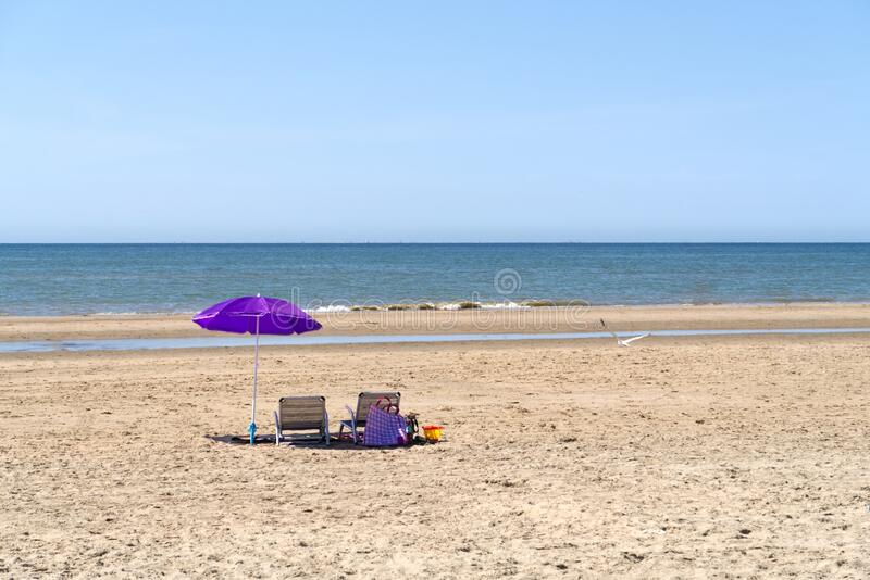Beach with umbrella and chairs stock photo