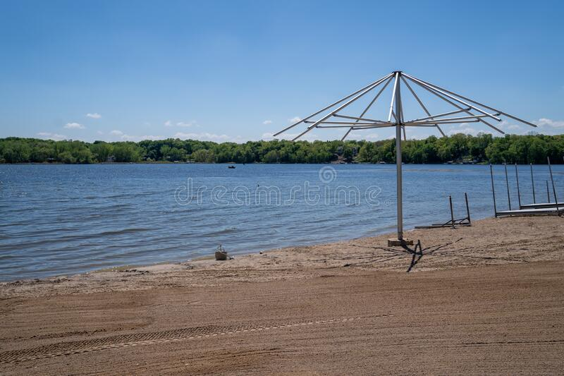 Beach umbrella, empty, sits on a lonely sandy beach on Clifton French Regional Park in Plymouth Minnesota. Beach umbrella, empty, sits on a lonely sandy beach on stock photography