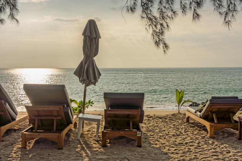 Beach umbrella and sunbath seats on Pak Weep beach. The beach is in Southern Thailand in the evening stock image