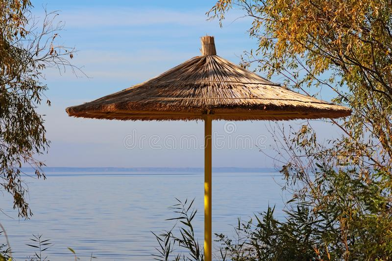 Beach umbrella with thatched roof near shore of a river on sunny autumn day stock images