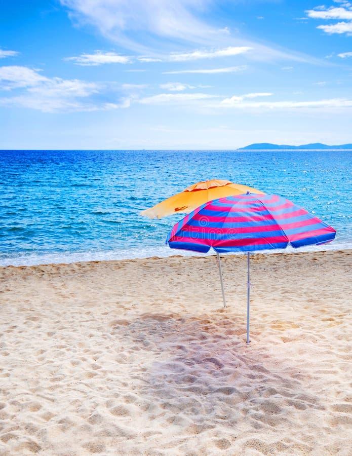 Beach Umbrellas. Two beach umbrellas on empty beach and bright blue ocean