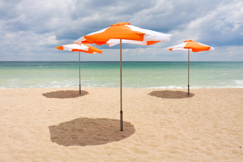 Beach umbrellas on the beach. Beach umbrellas on the white sand beach with cloudy blue sky and sun royalty free stock photo