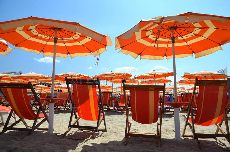 Beach umbrellas and chairs on beautiful beach in Marina di Pisa, Italy royalty free stock images