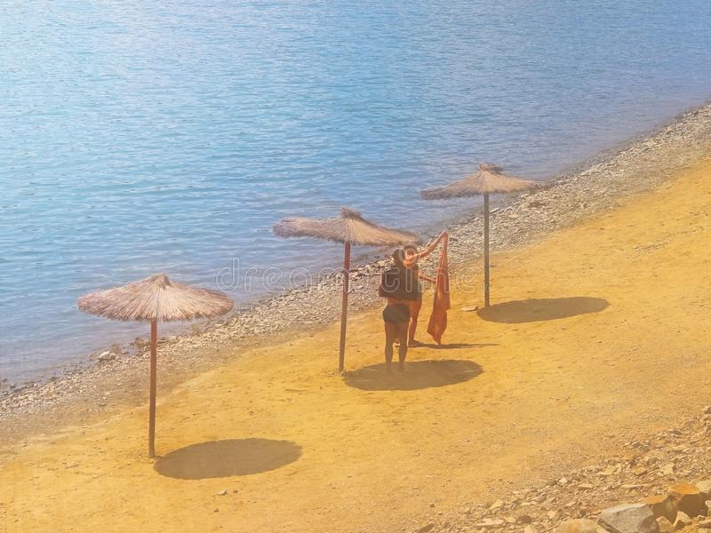 Beach with umbrellas from a creeper. Quality and comfort of rest at the water. Protection from sunlight. Rest on the beach and pon stock image