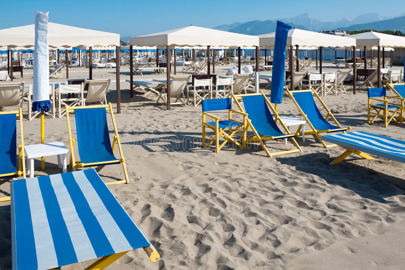 Beach umbrellas, deck chairs, tents on sand by sea royalty free stock images