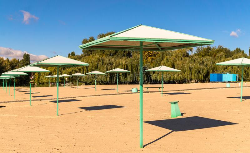 Beach umbrellas and deserted sandy beach in the early morning royalty free stock image