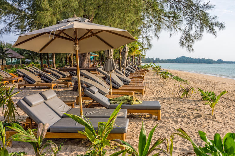 Beach umbrellas and sunbath seats on Pak Weep beach. The beach is in Southern Thailand stock images