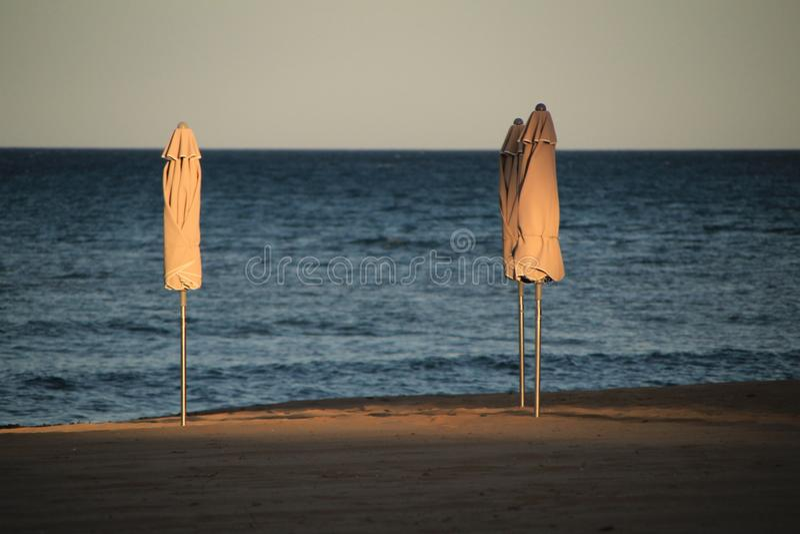 Beach umbrellas on the beach at sunset royalty free stock photos
