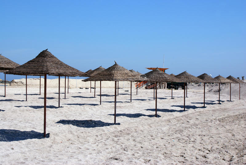 Beach umbrellas waiting tourists royalty free stock image