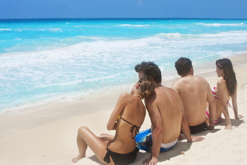 Beach Vacation. Two couples sitting on the beach enjoying the view of the Caribbean Ocean stock photo