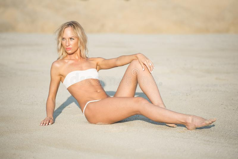 Beach vacation. Beautiful girl wearing white bikini in sun hat relaxing on the beach stock photos