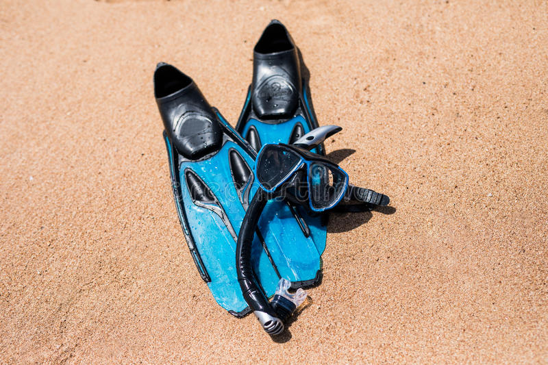 Beach vacation fun snorkel equipment on sand with ocean waves splashing water. Scuba diving and snorkelling. Black Flippers, black. Mask, snorkel on sandy stock photo