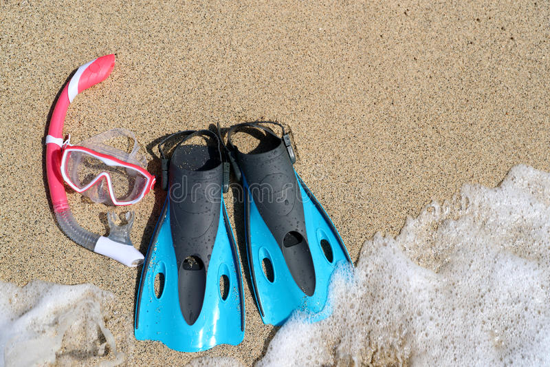 Beach vacation snorkel equipment flippers and mask. Beach vacation activity: snorkel equipment for women. Scuba diving and snorkelling. Blue Flippers, pink mask stock images