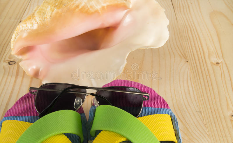 Beach vacation. Sunglasses, flip flops, sea shell on wooden background. Beach vacation. Beach accessories. Sunglasses, flip flops, sea shell on wooden background royalty free stock image