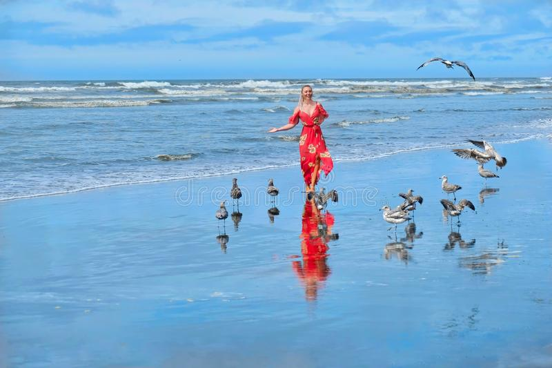 Beach vacation. Woman running on beach by sea with seagulls. royalty free stock photo