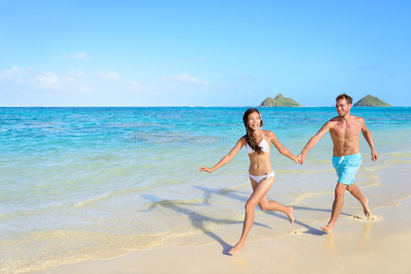 Beach vacations - happy holidays in Hawaii. Beach vacations - happy couple running together joyful in water during holidays in Hawaii stock photography