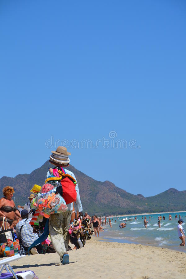 Beach vendors. Vendor selling children's beach toys, hats and head scarfs walking on the crowded beach in Italy; Costa Rei Beach in Sardinia, Italy; 09.09.2011 stock photo